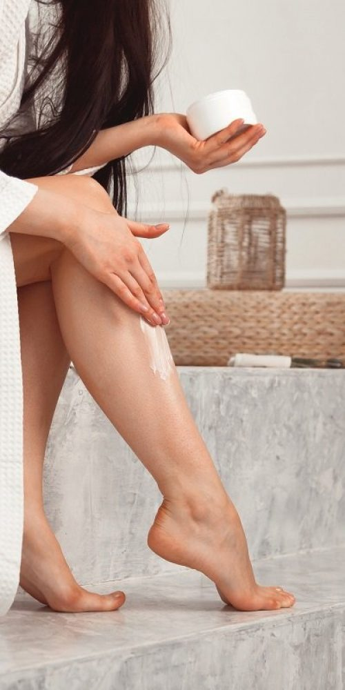 young-brunette-woman-applying-body-scrub-or-cream--CABZE3X